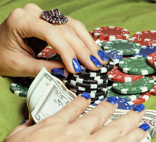 An image of hands of young caucasian woman with blue manicure at casino table close up, deep indigo design on nails
