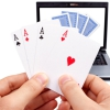 An image of poker in the hand and on a laptop screen