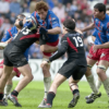 An image of rugby players on the field involved in a tackle